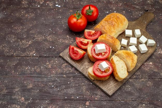 Vista dall'alto fresco gustoso pane lungo panino formato pasta tagliata con formaggio e pomodori sulla scrivania in legno marrone panino pasta pasta pane farina