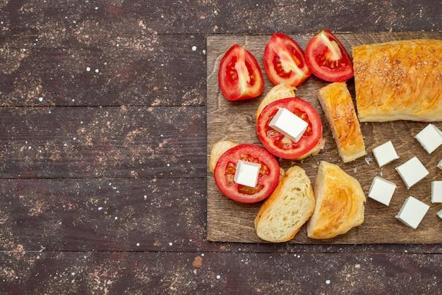 Vista dall'alto pane gustoso fresco lungo panino formato pasta tagliata con formaggio e pomodori sulla farina di pane di pasta sfoglia di legno marrone scrivania