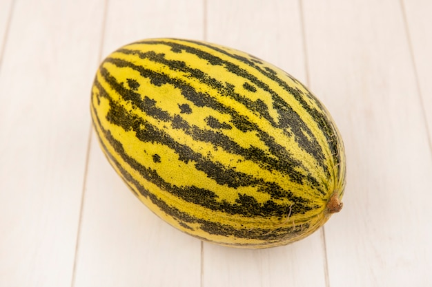 Top view of fresh tasty cantaloupe melon isolated on a white wooden surface