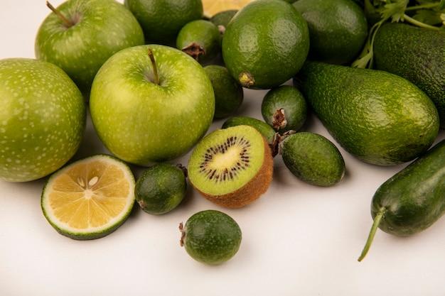Vista dall'alto di frutta fresca e gustosa come mele avocado limes feijoas isolato su uno sfondo bianco