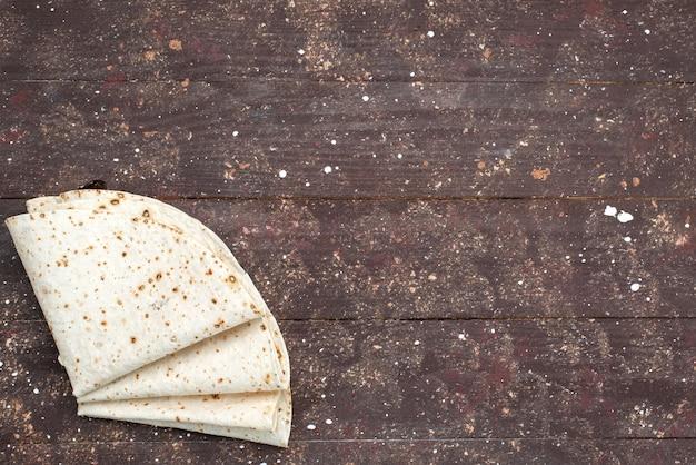 Вид сверху свежий вкусный лаваш на коричневом деревянном столе, тесто, булочка, хлеб, еда, еда