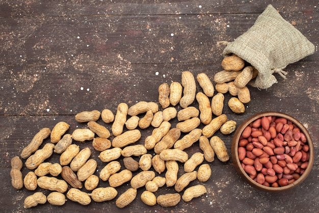 Вид сверху свежие вкусные орехи выкладывают на коричневый деревянный стол
