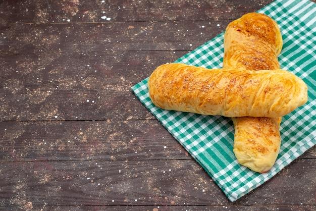 Vista dall'alto fresca gustosa pasticceria panino formato pasticceria sul tessuto a scacchi sulla scrivania in legno marrone panino pasta pasta pane farina alimentare