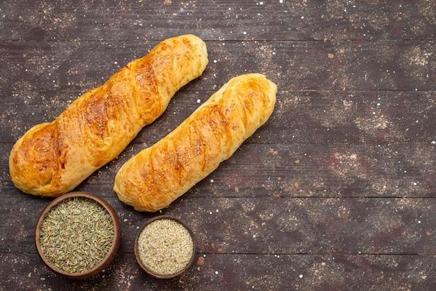 Vista dall'alto fresca gustosa pasticceria panino formato pasticceria con condimenti sulla scrivania in legno marrone panino pasta pasta pane pasto alimentare