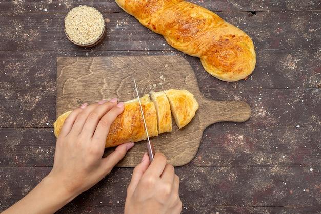 Panino lungo della pasticceria saporita fresca di vista superiore formata che ottiene la pasta tagliata sulla farina di pane della pasta della pasta del panino della scrivania di legno marrone