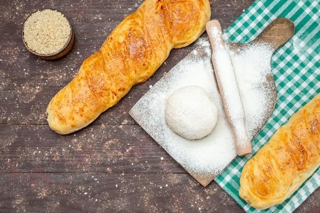 Vista dall'alto pasta fresca gustosa panino lungo formato pasta sul tessuto a scacchi con farina sulla scrivania in legno marrone panino pasta pasta pane cibo pasto