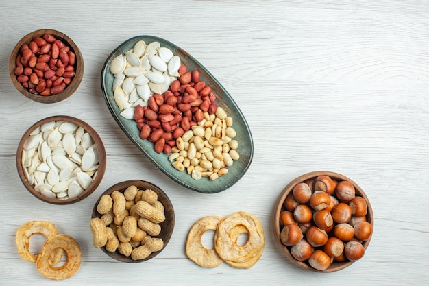 Вид сверху свежий вкусный арахис с белыми семенами и фундуком на светлом столе
