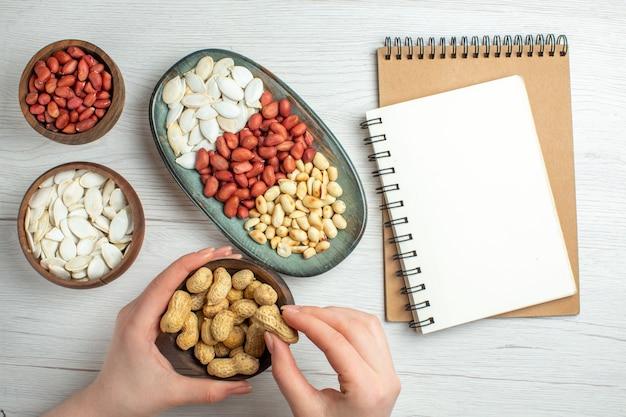Вид сверху свежий вкусный арахис с белыми семенами и блокнот на белом столе