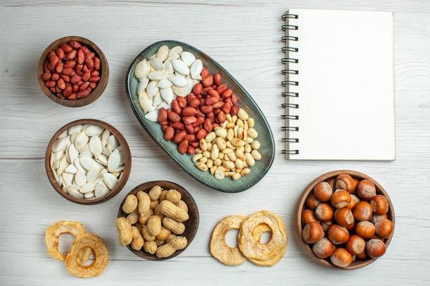 Vista dall'alto gustose arachidi fresche con semi bianchi e nocciole su un tavolo bianco chiaro