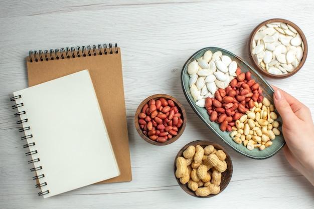 Вид сверху свежий вкусный арахис с белыми семенами внутри тарелки на белом столе