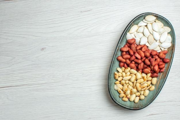 上面図白いテーブルの上のプレートの内側に白い種と新鮮なおいしいピーナッツ