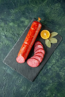 Top view fresh tasty sausage whole and sliced on blue background meat food burger bread bun color