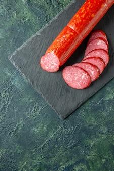 Vista dall'alto salsiccia fresca e gustosa intera e affettata su sfondo blu carne cibo hamburger panino pane colore panino