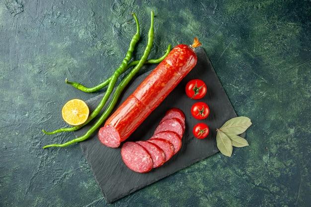 Vista dall'alto salsiccia fresca e gustosa con pomodori rossi su sfondo blu pane carne cibo panino panino insalata color