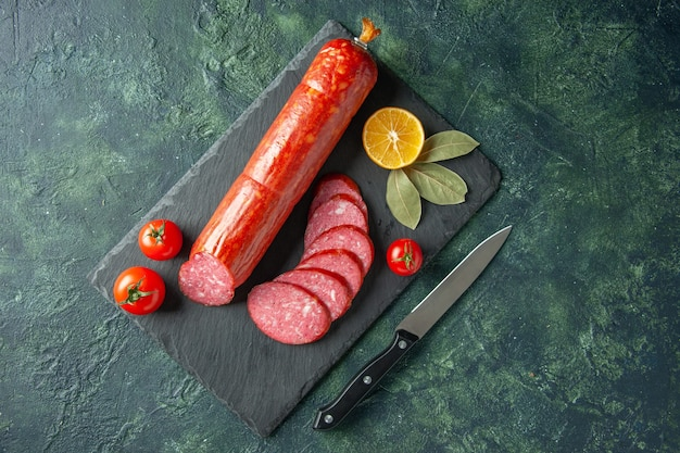 Top view fresh tasty sausage with tomatoes on blue background meat food burger sandwich bread bun color