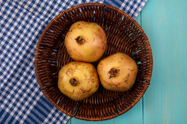 Top view of fresh three pomegranates on a bucket on a checked cloth on a blue wooden background