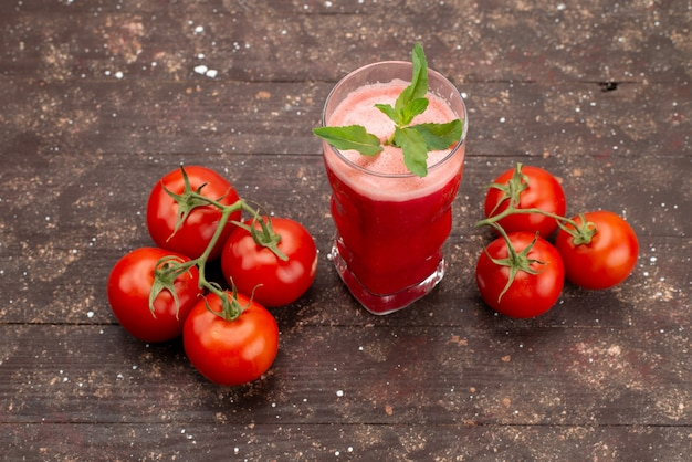 Top view fresh tomatoe juice with leaf along with whole tomatoes on brown