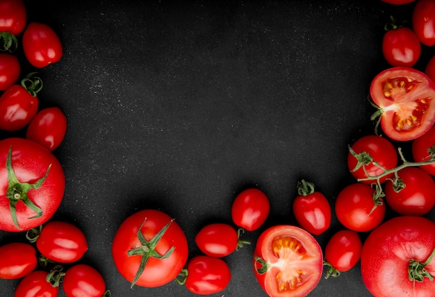 Top view of fresh tomatoes on black background with copy space