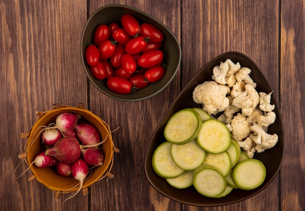 Top view of fresh tomatoes on a bowl with radishes on a bucket with chopped zucchinis and cauliflower buds on a bowl on a wooden background