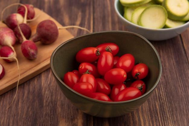 Vista dall'alto di pomodori freschi su una ciotola con ravanelli su una tavola da cucina in legno con zucchine tritate su una ciotola su una superficie di legno