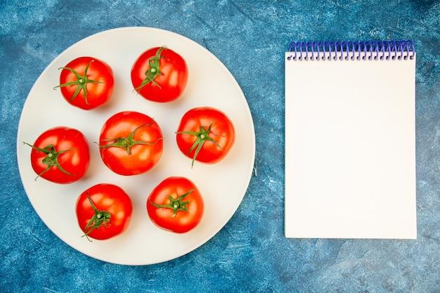 青いテーブルの上のプレート内のトップビューフレッシュトマト
