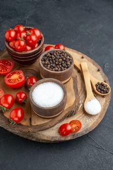 Vista dall'alto di pomodori freschi e spezie in ciotole cucchiai su tavola di legno su superficie nera