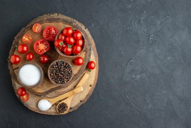 Vista dall'alto di pomodori freschi e spezie su tavola di legno sul lato destro sulla superficie nera