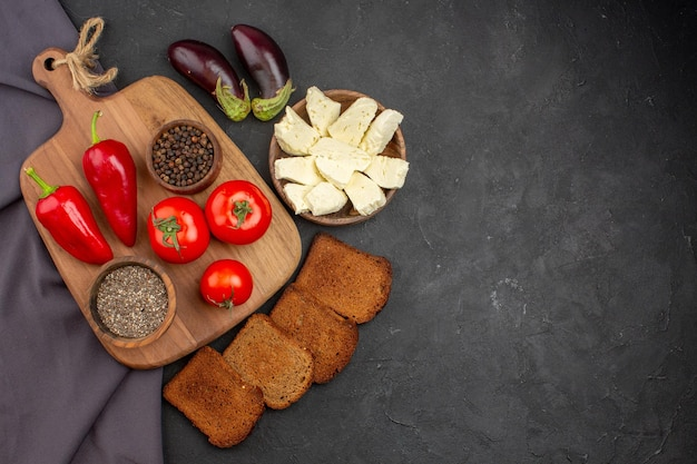 Top view of fresh tomatoes with dark. bread loafs and white cheese on black