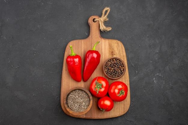 Top view of fresh tomatoes with seasonings on black