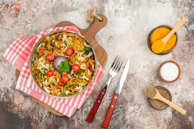 Vista dall'alto di insalata vegana fresca di varie verdure su un asciugamano spogliato rosso
