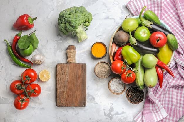 Vista dall'alto composizione di verdure fresche all'interno del piatto su sfondo bianco chiaro
