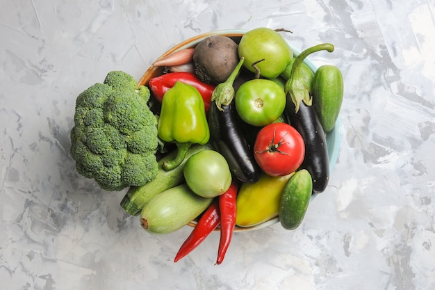 Top view fresh vegetable composition inside plate on white background