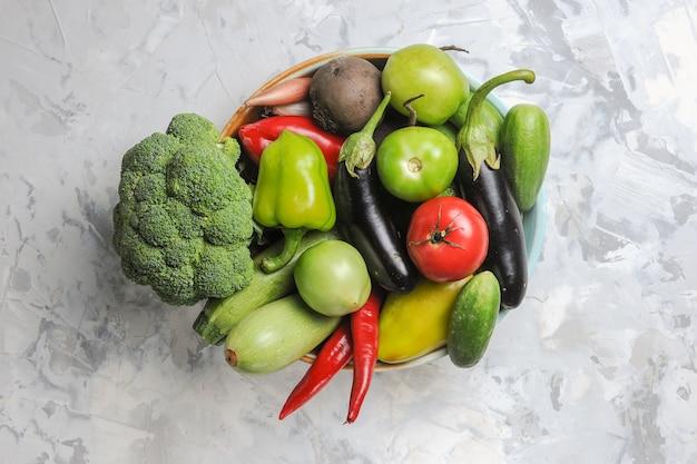 Vista dall'alto composizione di verdure fresche all'interno della piastra su sfondo bianco