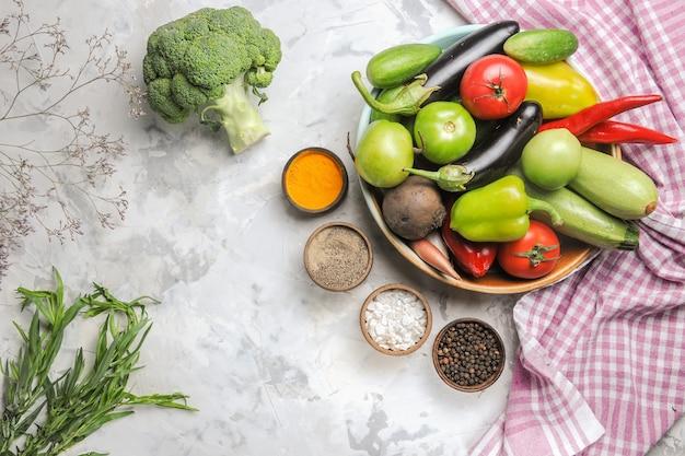 Vista dall'alto composizione di verdure fresche all'interno del piatto sullo scrittorio bianco