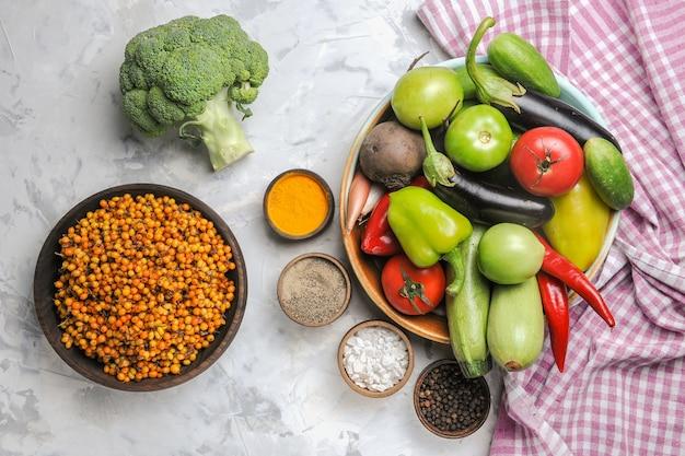 Vista dall'alto composizione di verdure fresche all'interno del piatto sul pavimento bianco