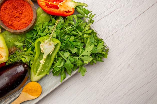 上面図白いテーブルに緑と調味料と新鮮な野菜の組成物