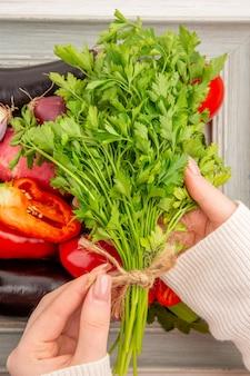 白いテーブルの上のフレームの内側に緑と野菜の組成物の上面図