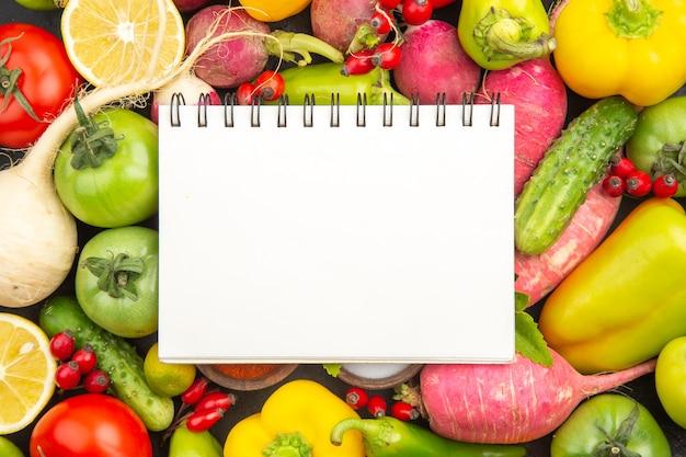 Vista dall'alto composizione di verdure fresche con condimenti e blocco note su sfondo scuro