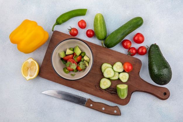 Top view of fresh vegetable like chopped cucumber cherry tomatoes yellow bell pepper and lemon on kitchen board with knife on white