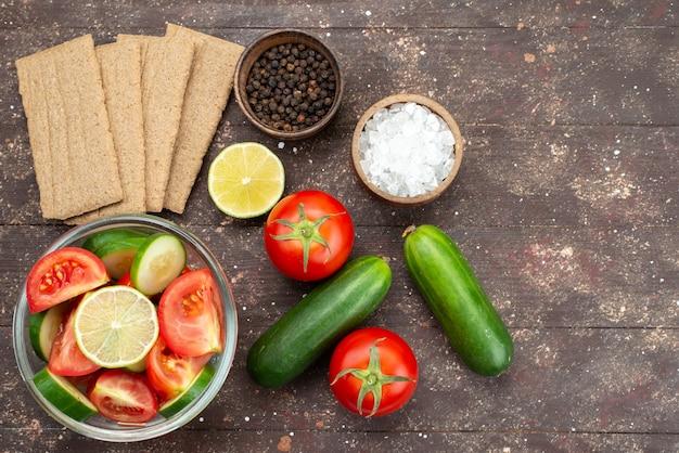 Vista dall'alto insalata di verdure fresche all'interno di vetro con limone insieme a patatine fresche di verdure intere su marrone