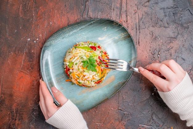 暗いテーブルの上のプレート内の上面の新鮮な野菜サラダ