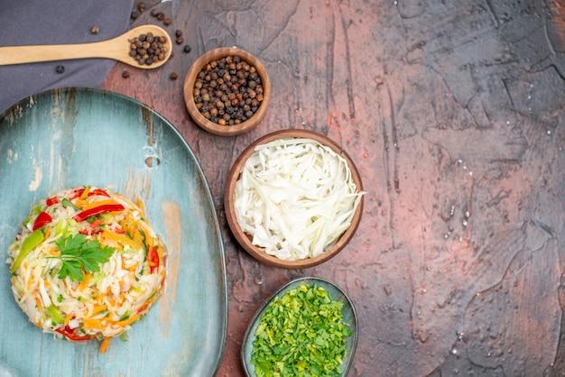 暗いテーブルの空きスペースに緑とプレート内の新鮮な野菜サラダの上面図