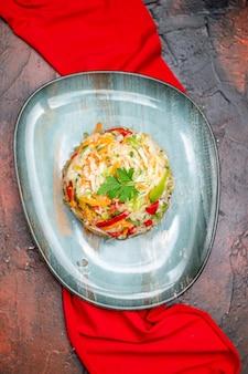 暗いテーブルの上の赤いティッシュとプレート内の新鮮な野菜サラダの上面図