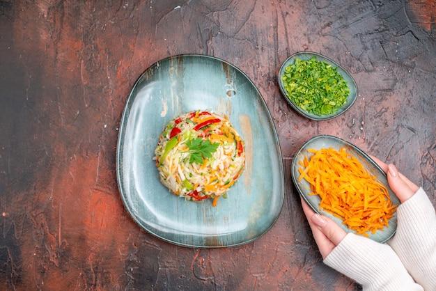 Insalata di verdure fresche vista dall'alto all'interno del piatto con carote affettate e verdure sul tavolo scuro