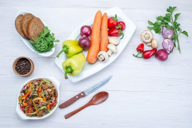 Vista dall'alto di insalata di verdure fresche a fette con carne insieme a pagnotte di pane e verdure intere e verdi sulla scrivania leggera, insalata di farina alimentare vitamina