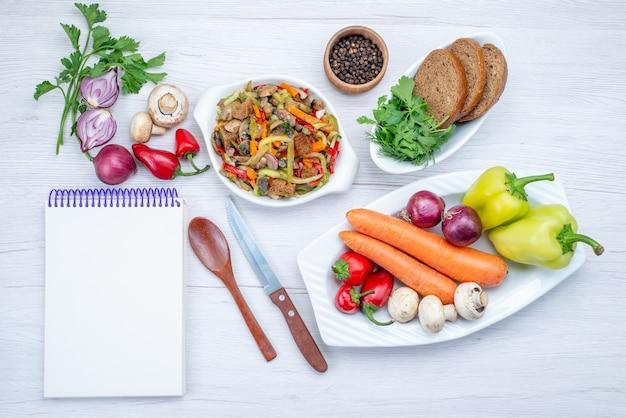 Vista dall'alto di insalata di verdure fresche a fette con carne insieme a pagnotte di pane e verdure intere e verdure sulla scrivania leggera, insalata di farina di verdure