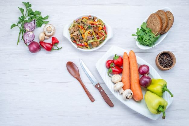 Vista dall'alto di insalata di verdure fresche a fette con carne insieme a pagnotte di pane e verdure intere e verdi sulla scrivania leggera, insalata di verdure