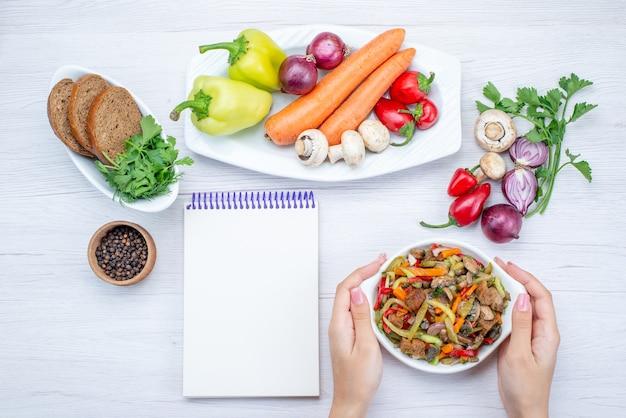 Vista dall'alto di insalata di verdure fresche a fette con carne insieme a pagnotte di pane e verdure intere e verdure su piatto leggero, insalata di cibo