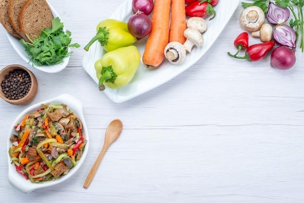 Vista dall'alto di insalata di verdure fresche a fette con carne insieme a pagnotte di pane e verdure intere e verdi su luce, insalata di farina alimentare vitamina