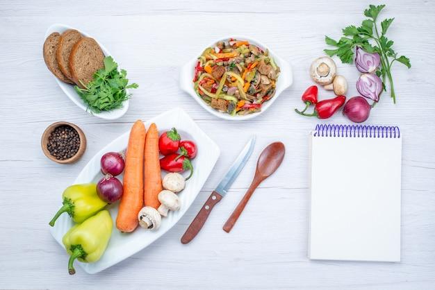 Vista dall'alto di insalata di verdure fresche affettata con carne insieme a pagnotte di pane e verdure e verdure intere su insalata di farina di cibo leggero e vegetale